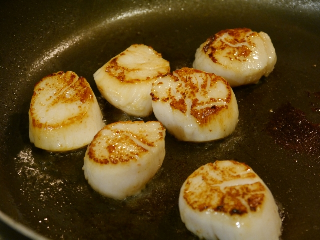 Sear the scallops in a hot pan with just a little bit of olive oil.  Don't touch them until you are ready to flip.  You'll get a nice crust like these have.